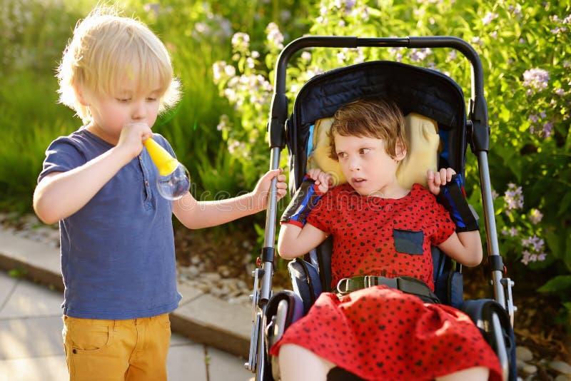 Weinig jongen en een gehandicapt meisje die samen in het de zomerpark spelen Kind hersenverlamming Familie met gehandicapt jong g stock afbeelding