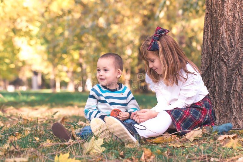 Weinig jongen en een meisje spelen openlucht stock foto's