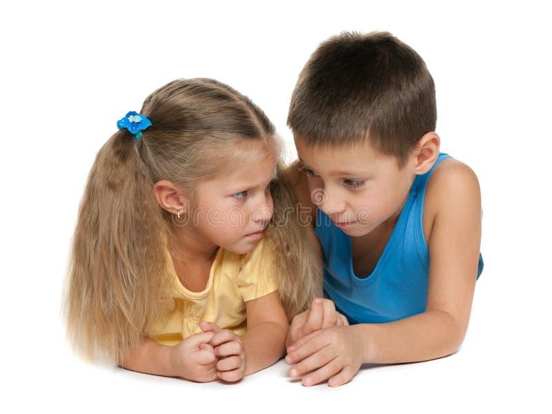 Weinig jongen en klein meisje liggen samen stock afbeelding