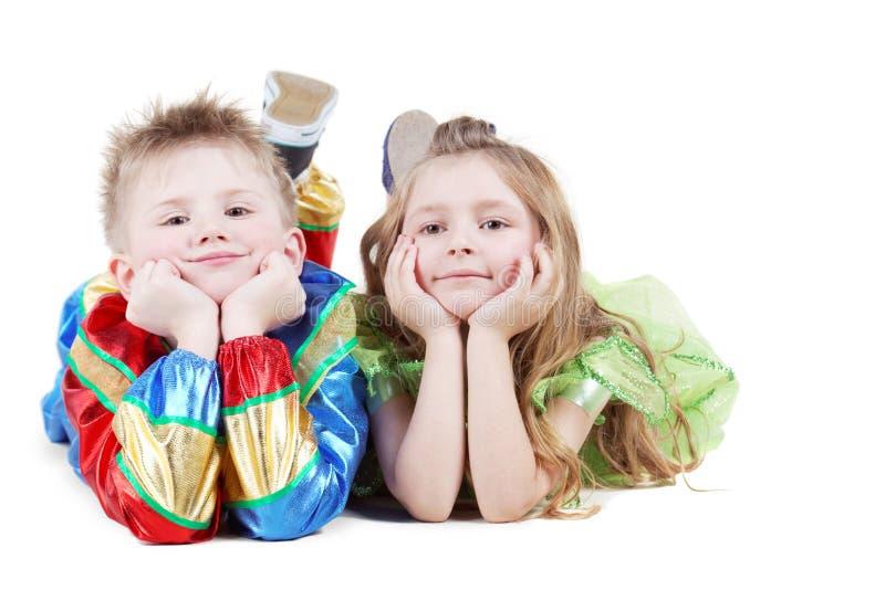 Weinig jongen en meisje in Carnaval kostuums liggen op vloer royalty-vrije stock fotografie