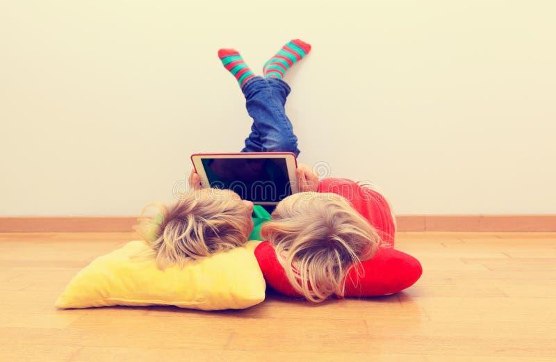 Weinig jongen en meisje die aanrakingsstootkussen bekijken, huis het leren stock afbeelding