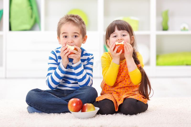 Weinig jongen en meisje die appelen eten stock foto's