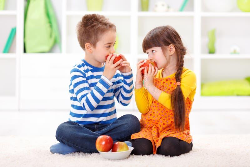 Weinig jongen en meisje die appelen eten royalty-vrije stock foto
