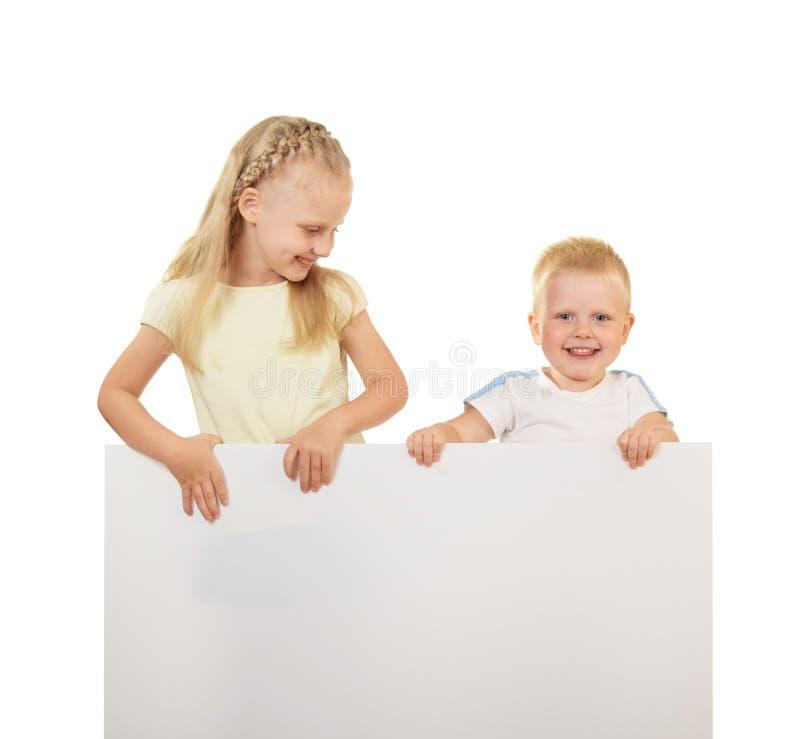 Weinig jongen en meisje die en lege banner glimlachen houden die op witte achtergrond wordt geïsoleerd royalty-vrije stock fotografie