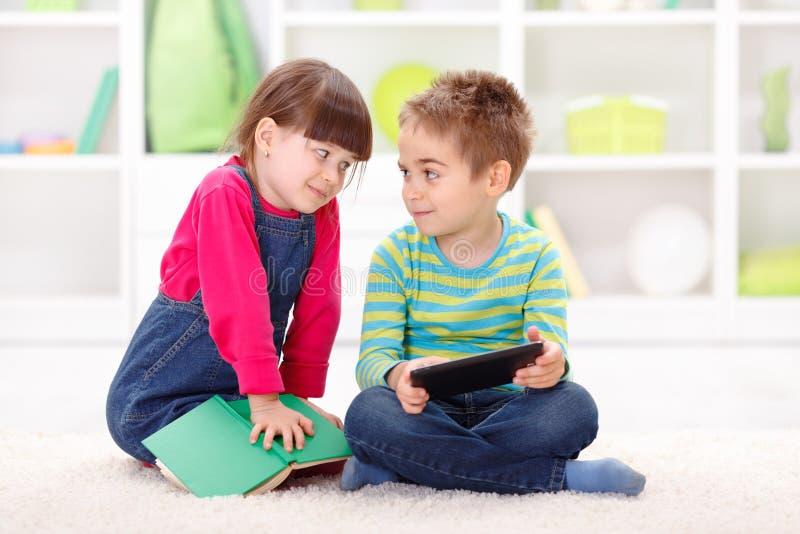 Weinig jongen en meisje die of van tablet spelen lezen stock foto