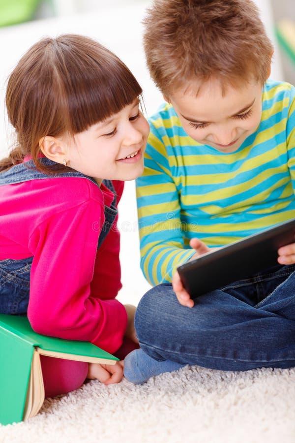 Weinig jongen en meisje die of van tablet spelen lezen royalty-vrije stock fotografie