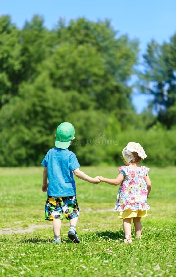 Weinig jongen en meisje hand in hand stock afbeeldingen