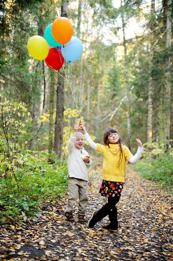Weinig jongen en meisje met ballons in een bos stock foto