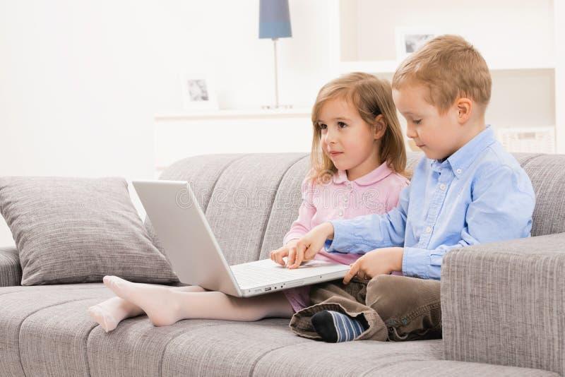 Weinig jongen en meisje met laptop stock foto