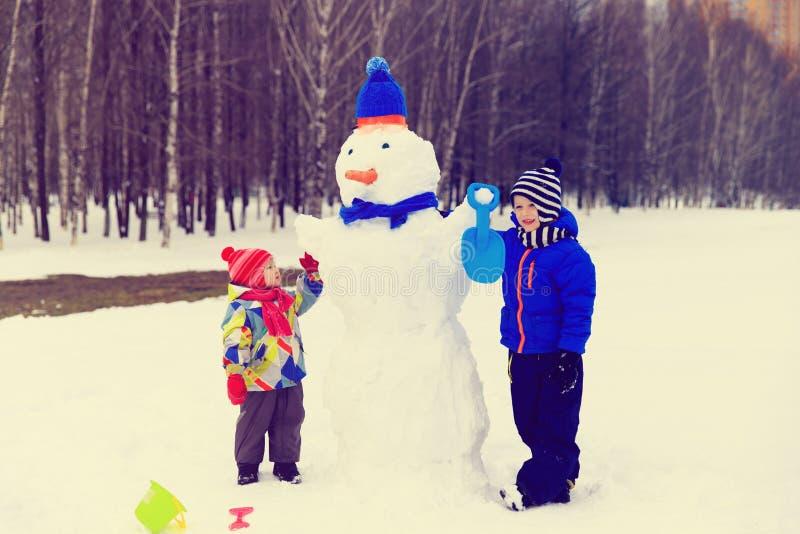 Weinig jongen en meisje spelen met sneeuwman in de winteraard royalty-vrije stock foto's
