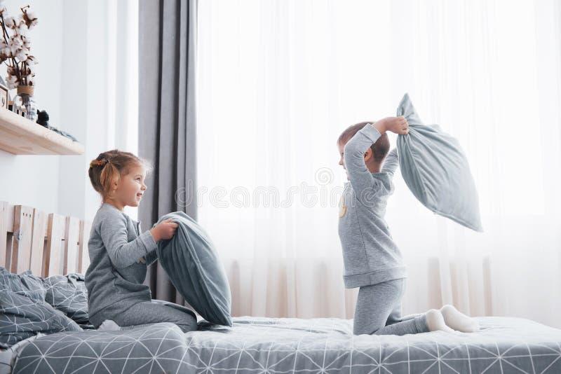 Weinig jongen en meisje voerden een hoofdkussenstrijd op het bed in de slaapkamer op De ongehoorzame kinderen slaan elkaar hoofdk royalty-vrije stock fotografie