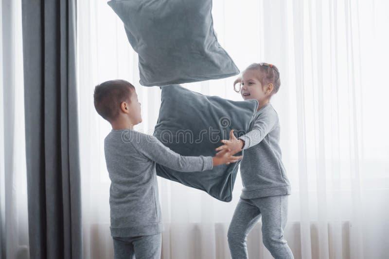 Weinig jongen en meisje voerden een hoofdkussenstrijd op het bed in de slaapkamer op De ongehoorzame kinderen slaan elkaar hoofdk royalty-vrije stock foto's