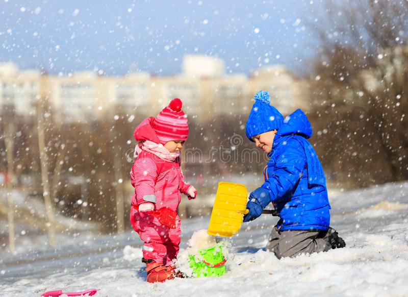 Weinig jongen en meisjes gravende sneeuw in de winter stock foto