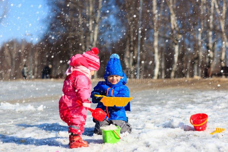 Weinig jongen en meisjes gravende sneeuw in de winter royalty-vrije stock afbeelding