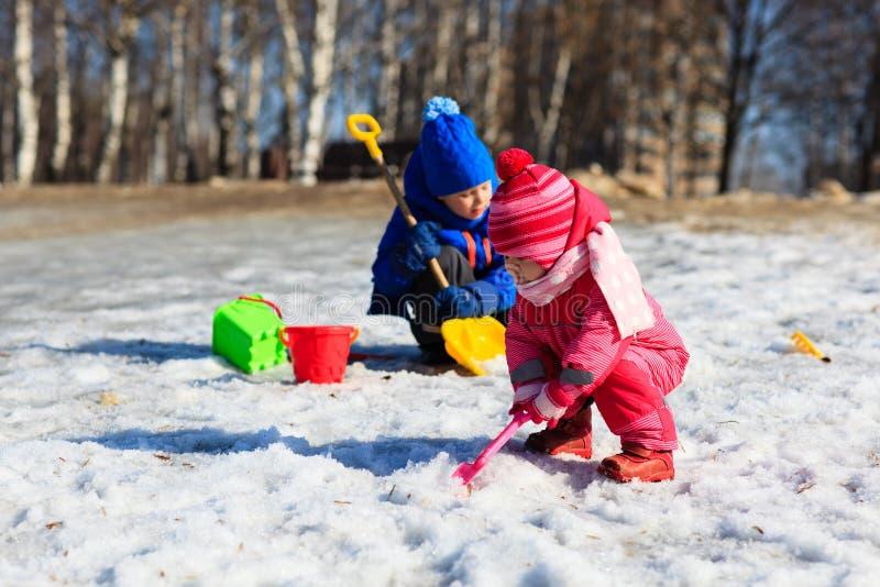 Weinig jongen en meisjes gravende sneeuw in de winter stock fotografie
