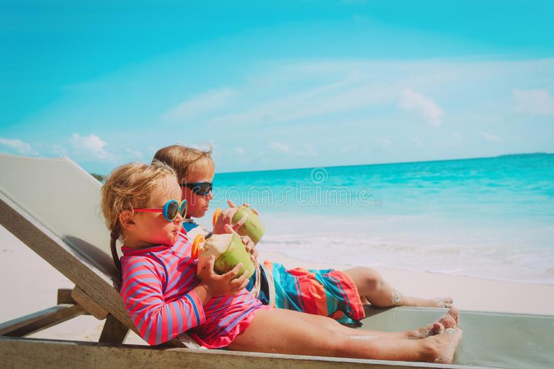 Weinig jongen en meisjes het drinken kokosnoot op strandvakantie royalty-vrije stock foto
