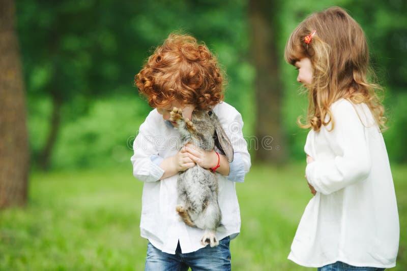 Weinig jongen en meisjes het spelen met konijn stock afbeeldingen