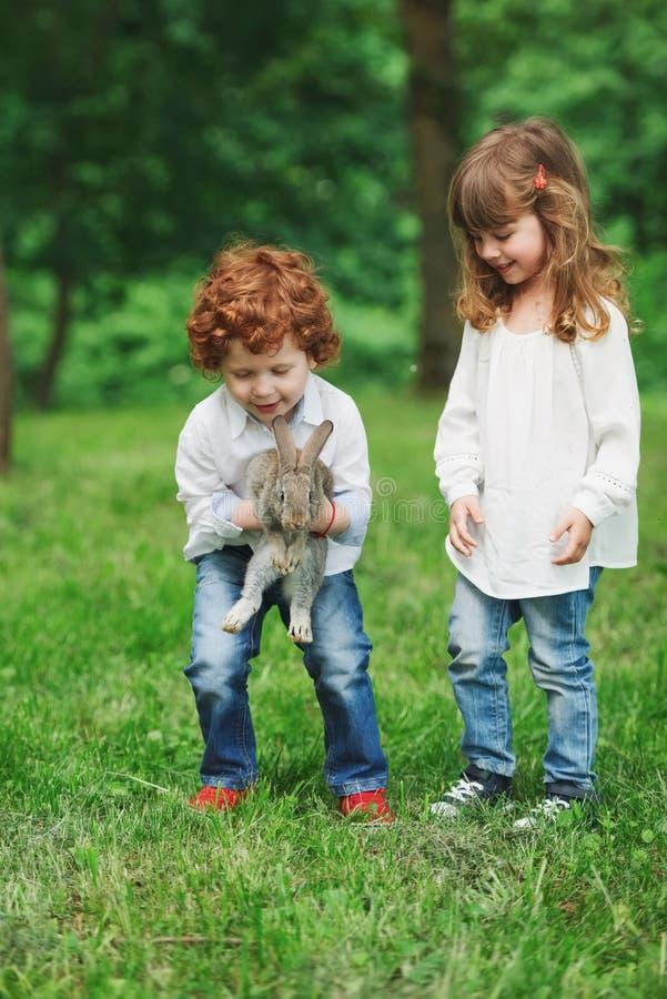 Weinig jongen en meisjes het spelen met konijn royalty-vrije stock afbeelding
