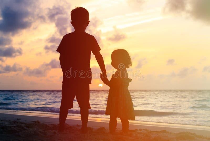 Weinig jongen en meisjesholdingshanden bij zonsondergang stock foto's