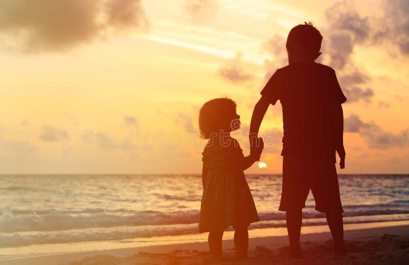 Weinig jongen en meisjesholdingshanden bij zonsondergang stock afbeeldingen
