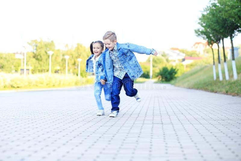 Weinig jongen en meisjeslooppas, die handen houden Het concept kinderjaren, familie, onderwijs royalty-vrije stock foto