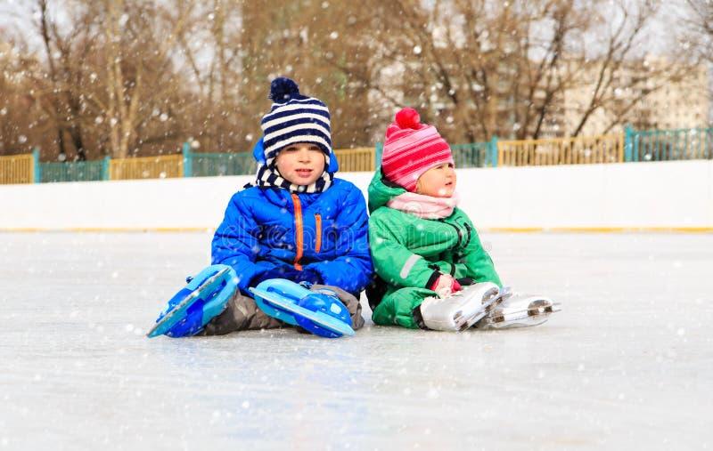 Weinig jongen en meisjeszitting op ijs met vleten stock afbeelding