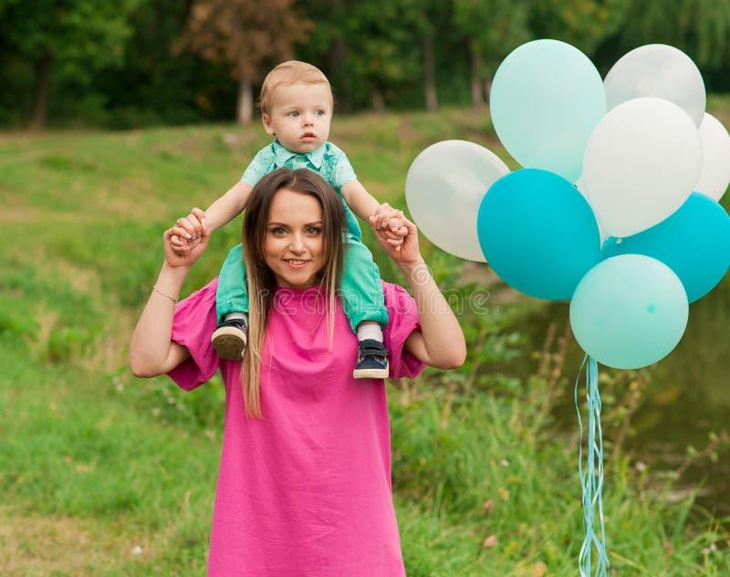 Weinig jongen en moeder in de herfstaard met kleurrijke ballon royalty-vrije stock fotografie