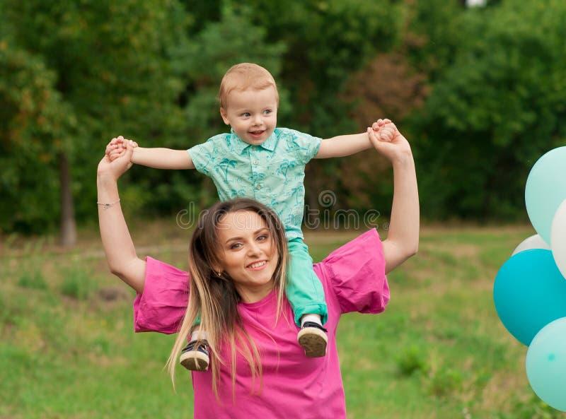 Weinig jongen en moeder in de herfstaard met kleurrijke ballon royalty-vrije stock afbeelding