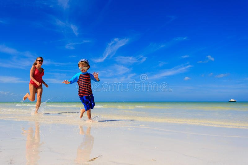 Weinig jongen en moeder die op strand lopen stock fotografie