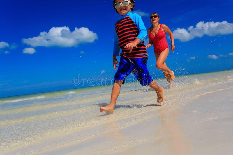 Weinig jongen en moeder die op strand lopen stock foto's