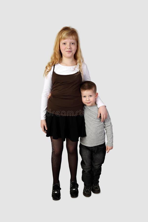 Weinig jongen en oudere omhelste meisjestribune stock foto