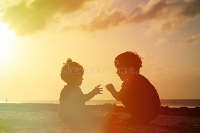 Weinig jongen en peutermeisje het spelen bij zonsondergang royalty-vrije stock afbeeldingen