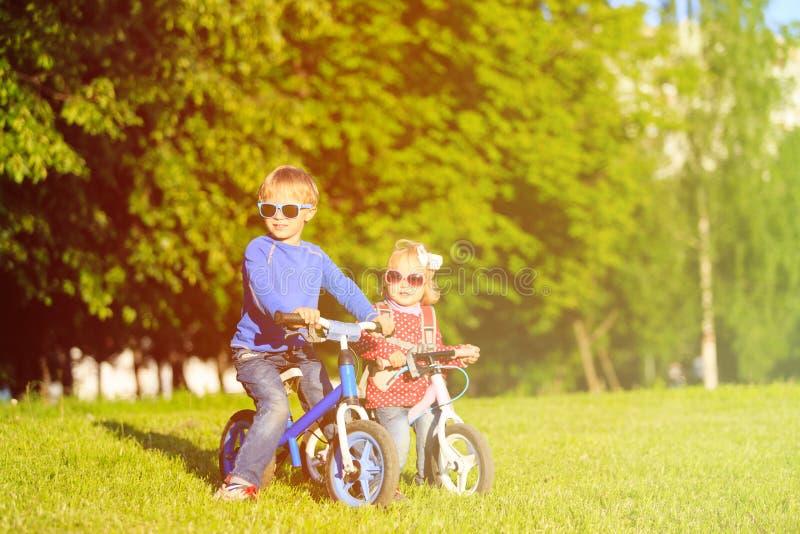 Weinig jongen en peutermeisje op fietsen in de zomer royalty-vrije stock foto's