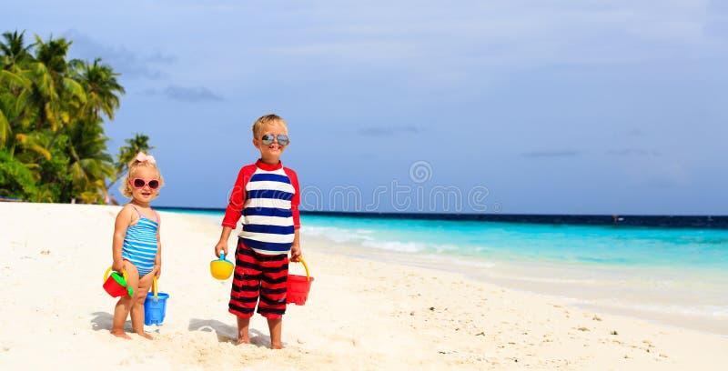 Weinig jongen en peutermeisje speelt met zand stock foto