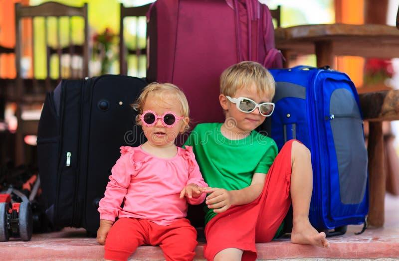 Weinig jongen en peutermeisjeszitting op koffers klaar te reizen royalty-vrije stock foto's