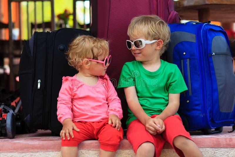 Weinig jongen en peutermeisjeszitting op koffers klaar te reizen royalty-vrije stock fotografie