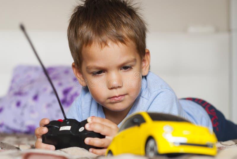Weinig jongen en stuk speelgoed auto stock afbeelding