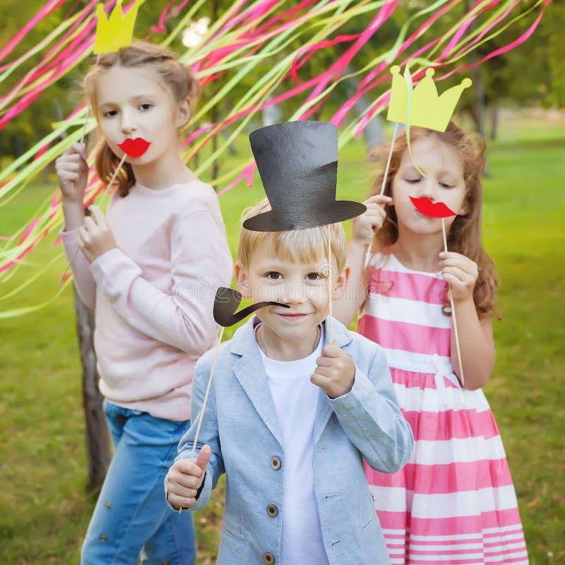 Weinig jongen en twee meisjes die met document maskers op een vrolijke vakantie van kinderen stellen stock afbeelding