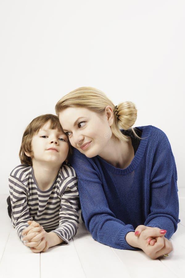 Weinig jongen en zijn moeder die dicht bij elkaar op de witte achtergrond liggen royalty-vrije stock foto