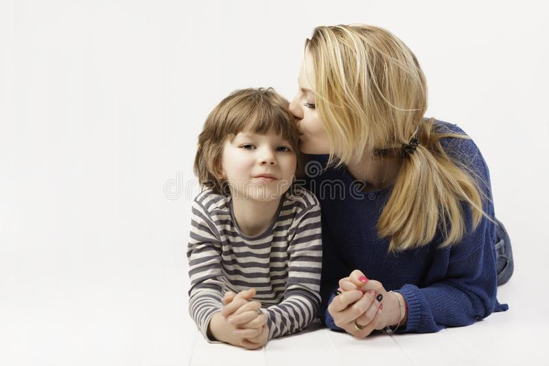 Weinig jongen en zijn moeder die, moeder die haar zoon, andere op de witte achtergrond kussen liggen royalty-vrije stock afbeeldingen