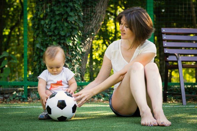 Weinig jongen en zijn moeder die met voetbalbal bij opleidingsgrond spelen Mamma en zoonsspel samen bij voetbalgebied in openluch royalty-vrije stock foto's