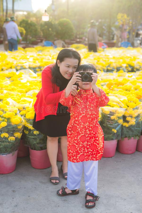 Weinig jongen en zijn mooie jonge moeder die beeld met de digitale fotocamera nemen Gelukkige familie die foto in Tet-bloem maken royalty-vrije stock afbeelding
