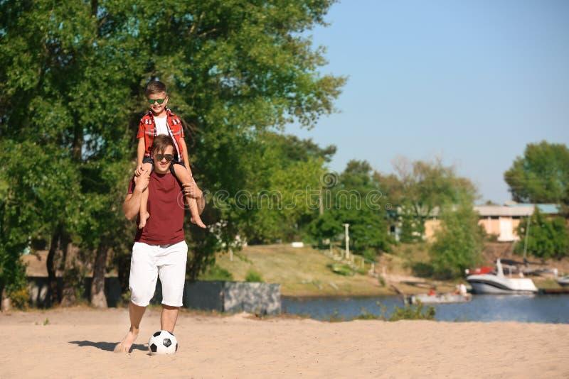 Weinig jongen en zijn papa met voetbalbal op zandstrand stock fotografie