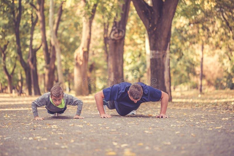 Weinig jongen en zijn vader die duwups oefeningen samen in het park doen royalty-vrije stock foto's