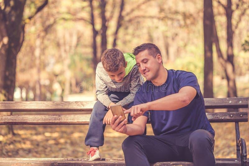 Weinig jongen en zijn vader die een onderbreking na training nemen en smartphone in het park met behulp van royalty-vrije stock foto