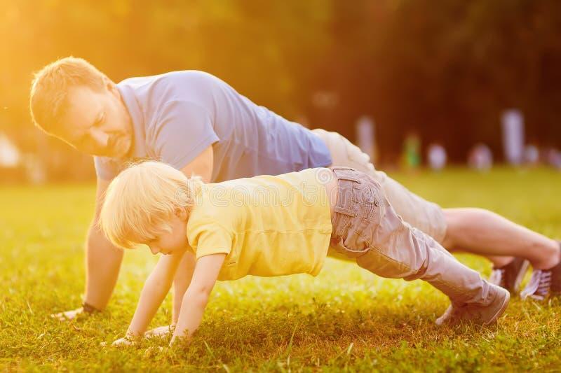 Weinig jongen en zijn vader die plank doen oefenen in zonnig de zomerpark uit stock foto