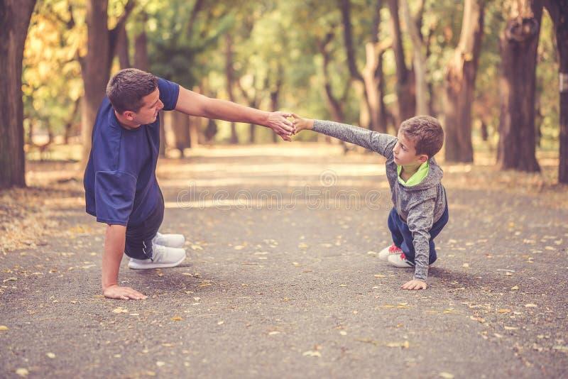 Weinig jongen en zijn vader die samen in openlucht uitoefenen royalty-vrije stock afbeeldingen