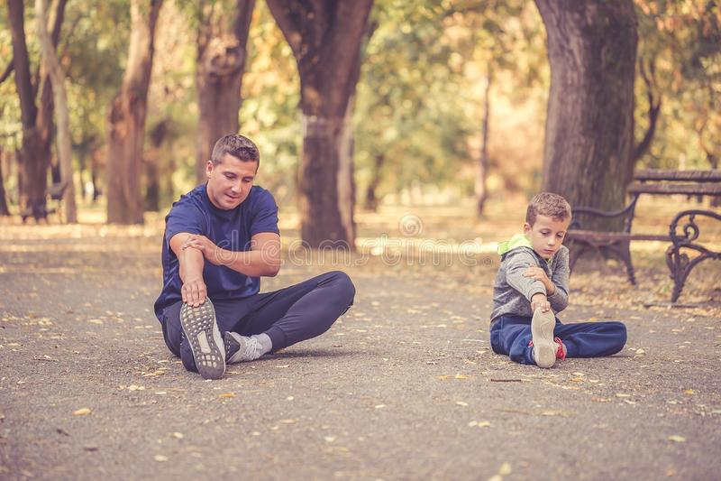 Weinig jongen en zijn vader die uitrekkende oefening samen in het park doen stock foto