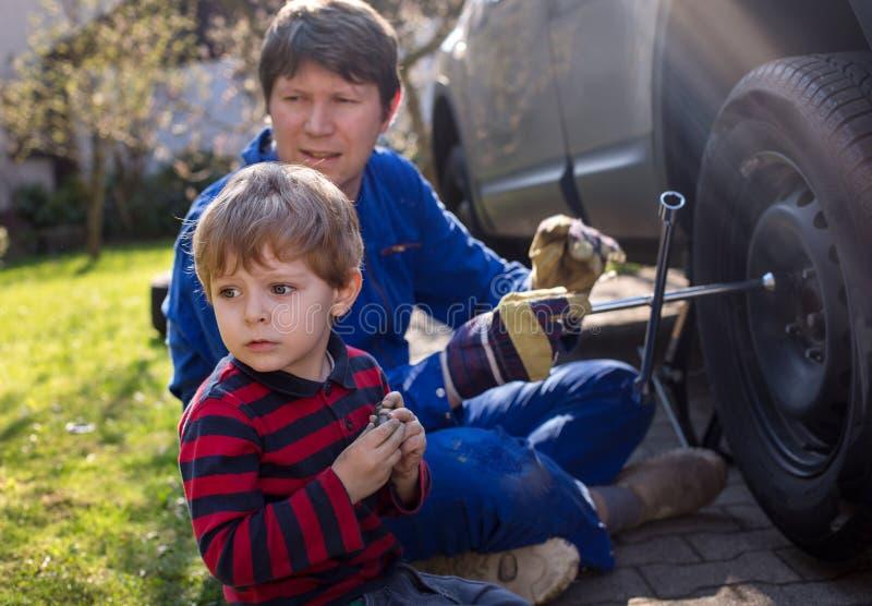 Weinig jongen en zijn vader veranderend wiel op auto stock afbeelding