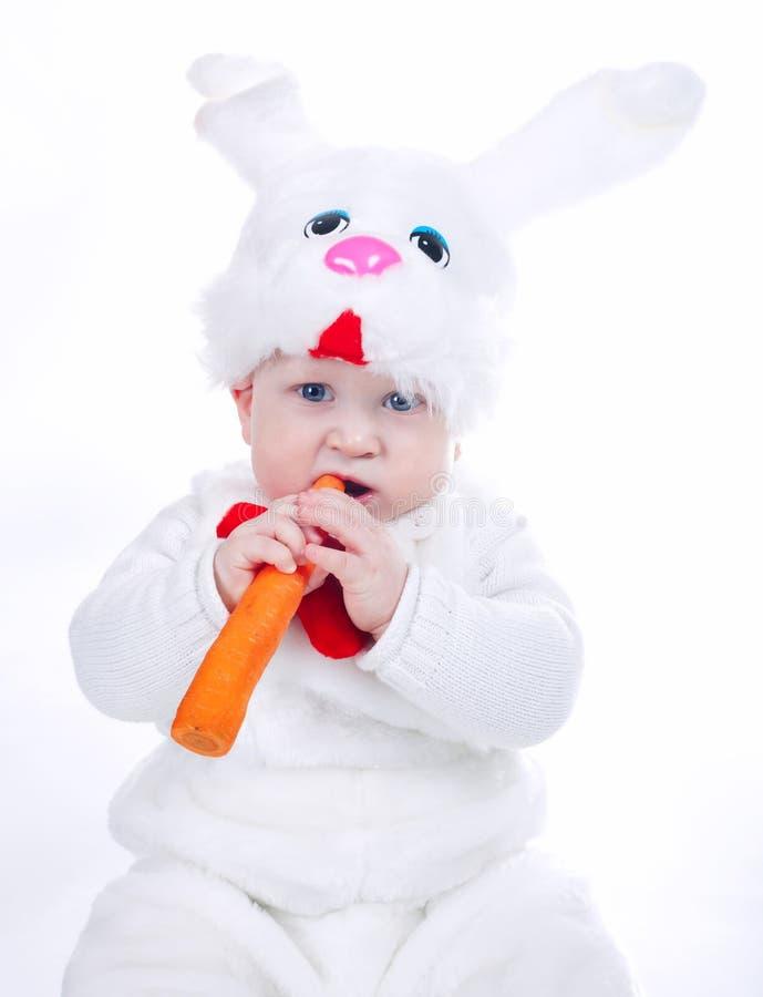 Weinig jongen in geïsoleerde konijnkostuum met wortel royalty-vrije stock afbeeldingen